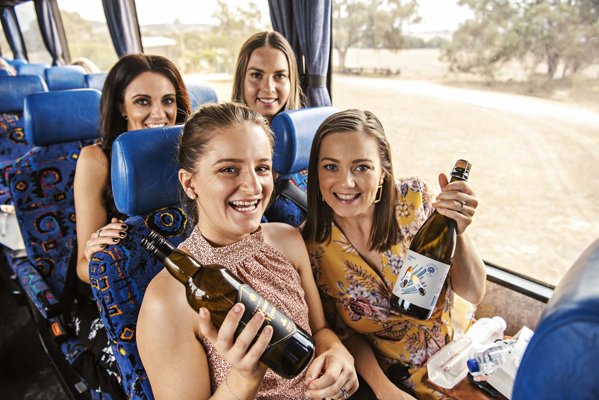 girls on wine tour bus holding wine